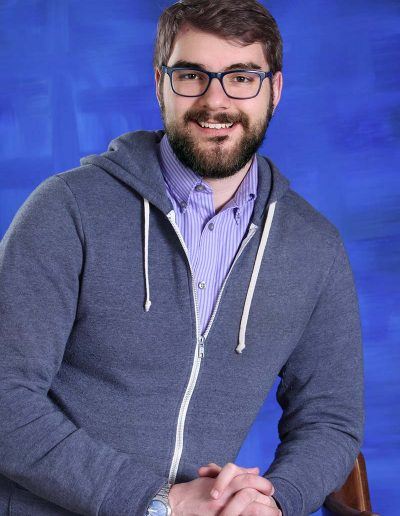 casual male headshot with blue background