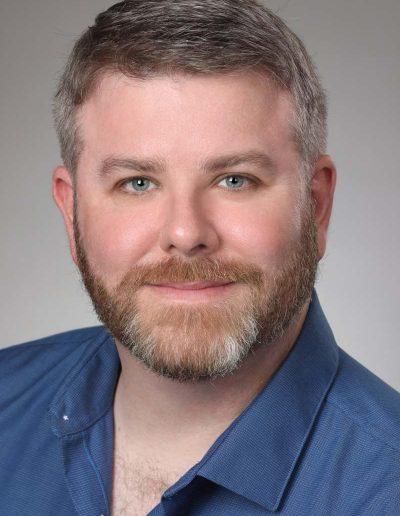 male executive headshot with grey background